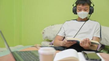 männlicher Student mit Maske, der ein Buch auf dem Bett liest, um sich auf die Prüfung vorzubereiten. Er lernte zu Hause, um Covid-19 zu schützen. foto