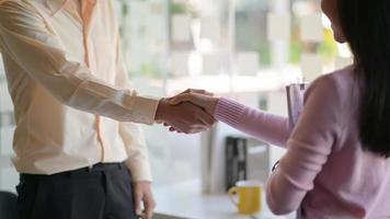 Männer und Frauen schütteln sich die Hände, um zusammenzuarbeiten. foto