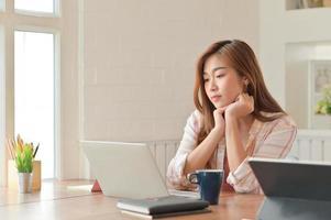 asiatische Studentin, die aufmerksam den Laptop liest. Sie bereitet sich auf die Abschlussprüfung vor. foto