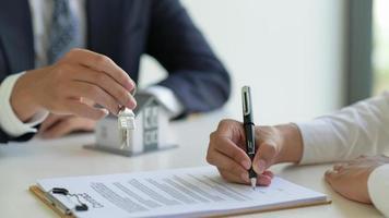Der Hausmakler empfiehlt dem Kunden, den Vertrag, das Immobilienkonzept, zu unterzeichnen. foto