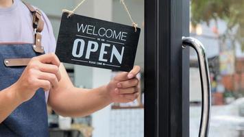 abgeschnittene Aufnahme von Geschäftsinhabern hält ein offenes Schild, um Service zu bieten. foto