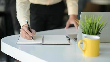 Hand schreibt eine Notiz auf ein Notizbuch mit einer Kaffeetasse und einem Laptop auf dem Schreibtisch. foto