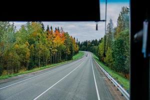 Blick auf die Straße und den herbstlichen Wald durch das Busfenster. Ausflug foto