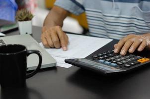 Geschäftsmann mit Taschenrechner an einem Schreibtisch. Unternehmensfinanzierung, Steuern und Investitionskonzepte. foto