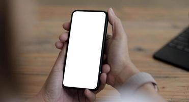 Mockup-Bild leerer weißer Bildschirm handy.women Hand hält SMS mit Handy auf dem Schreibtisch im Home Office. foto
