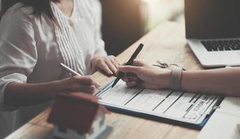 Hausmodell mit Agent und Kunde, die über einen Vertrag zum Kauf, zum Abschluss einer Versicherung oder zum Darlehen von Immobilien oder Eigentum diskutieren. foto
