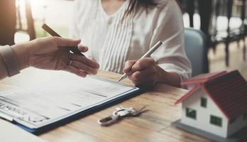 der immobilienmakler erklärt den kunden, die mit dem hausdesign und dem kaufvertrag, der bewilligung des hypothekendarlehens, dem wohnungsdarlehen und dem versicherungskonzept Kontakt aufnehmen, den hausstil. foto
