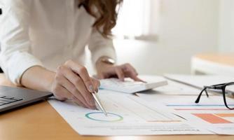 Geschäftsfrau, die mit Geschäftsdiagramm im Büro, Finanzberichtkonzept arbeitet. foto