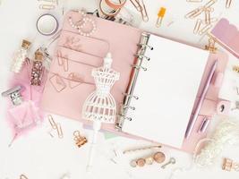 Draufsicht auf einen rosa Planer mit süßem Briefpapier. pinker Glamour-Planer mit weißer Schaufensterpuppe. Planer mit offenen Seiten auf weißem Hintergrund und mit schönem Zubehör Stifte, Knöpfe, Pins. foto