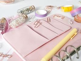 Roségold-Planer-Briefpapier. Planer mit schönem Zubehör Stifte, Knöpfe, Pins und farbiges Klebeband. gelber Stift und rosa Planer auf weißem Hintergrund. Kristalle in Glasflaschen neben dem Planer foto