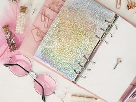 silberner Schlüssel auf der weißen Seite des Planers. Tagebuch offen mit weißer und holografischer Seite. rosa Planer mit süßem Briefpapier. Draufsicht auf den rosa Planer mit Briefpapier. foto