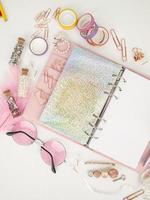 Tagebuch öffnet mit weißer und holografischer Seite. Rosa Planer mit süßem Briefpapier, das im Flatlay-Stil fotografiert. Draufsicht des rosa Planers mit Geschäftsbriefpapier. rosa Glamour-Planer Dekorationsfoto foto