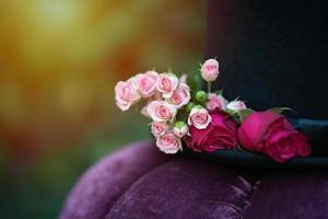 Alice im Wunderland. Hutzylinder mit Blumenrosen verziert. Nahaufnahme. weicher selektiver Fokus. foto