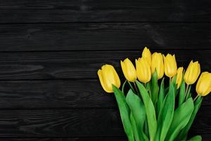 Bouquet von gelben Tulpen Frühlingsblumen auf schwarzem Holzhintergrund. flach liegen. Platz kopieren. Muttertag. Internationaler Frauentag. foto