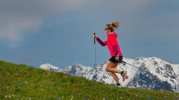 Nordic Walking und Trailrunning ein Mädchen mit Stöcken auf Frühlingsbrasse mit schneebedecktem Hintergrund foto