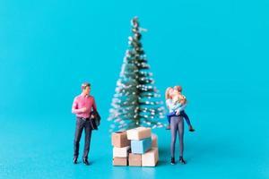 Miniaturmenschen, glückliche Familie, die neben einem Weihnachtsbaum steht foto