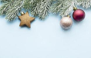 Weihnachtsminimalkonzept - Weihnachtskomposition mit schneebedecktem Tannenzweig und Kugeln foto