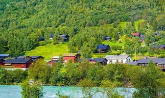 Türkisfarbenes Schmelzwasser fließt in einem Fluss durch ein Dorf in Norwegen foto