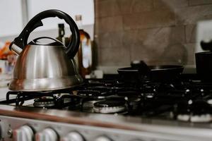 Selektive Fokusaufnahme von Teekessel mit kochendem Wasser auf einem Gasherd foto