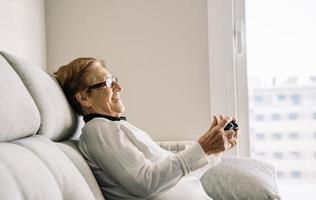 zufriedene ältere Frau mit Konsole, die Videospiele spielt foto