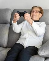 fröhliche ältere Frau, die Videospiel spielt foto