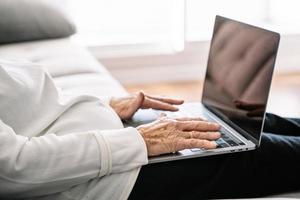 Ruhige ältere Frau, die Laptop im Wohnzimmer durchsucht foto