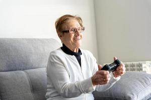 erfreute alte Frau, die ein Videospiel auf der Konsole spielt foto