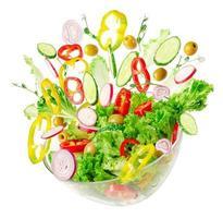 Salat aus frischem Gemüse in transparenter Schüssel mit fliegenden Zutaten, isoliert auf weiss. richtige Ernährung. foto