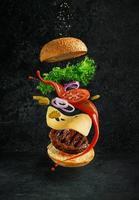 Hamburger mit schwimmenden Zutaten auf dunklem Hintergrund. kreatives Stilllebenkonzept und Werbung foto