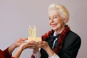 Fröhliche, stilvolle, achtundneunzig Jahre alte Frau im schwarzen Anzug, die ihren Geburtstag mit Kuchen feiert. Lifestyle, Positiv, Mode, Stilkonzept foto