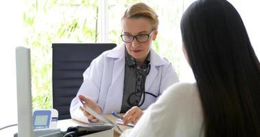 Arzttreffen und Erklärung der Medikamente für die Patientin in seinem Büro in Krankenhäusern foto