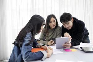 Gruppenschüler lächeln und haben Spaß und die Verwendung des Tablets hilft auch, Ideen in der Arbeit und im Projekt zu teilen. und rezensiere das Buch auch vor der Prüfung foto
