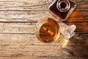 Cognac- oder Whiskygetränk auf rustikalem Holztisch foto