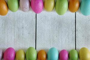 Oster- oder Frühlingshintergrund aus altem Holz und farbigen Eiern aufgereiht foto