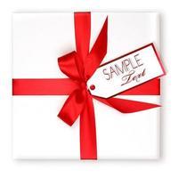 hübsch verpacktes Weihnachtsgeschenk mit roter Schleife und Geschenkanhänger foto