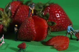 Bauarbeiter in konzeptionellen Essensbildern mit Erdbeeren foto