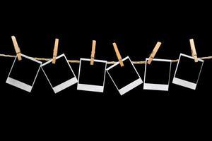 Polaroids hängen auf schwarzem Hintergrund foto