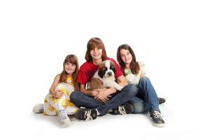Geschwisterkinder mit ihrem neuen Bernhardinerwelpen foto