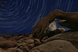 Night Star Trail Streaks über die Felsen des Joshua Tree Parks foto