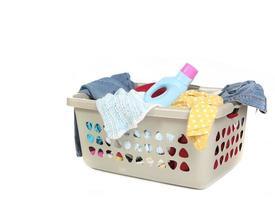 Korb voller schmutziger Wäsche mit Waschmittel foto