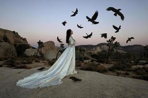 abstraktes Konzept eines Mädchens, umgeben von schwarzen Vögeln, die Fantasie darstellen foto