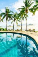 Wunderschöner Luxus-Sonnenschirm und -Stuhl um den Außenpool im Hotel und Resort mit Kokospalme bei Sonnenuntergang oder Sonnenaufgang foto