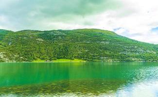 Türkisfarbenes Schmelzwasser fließt im Fluss durch die Gebirgslandschaft Norwegens foto
