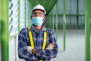 leitender Ingenieur, der eine Maske trägt, um neue Normalität zu arbeiten foto