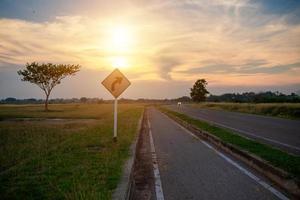 Verkehrsschilder und Radwege bei Sonnenuntergang foto
