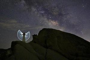 schöne frau licht gemalt mit dem nächtlichen himmel posiert foto