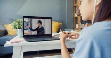Nahaufnahme junges asiatisches Mädchen mit Freizeitkleidung Kopfhörer verwenden Computer-Laptop-Videoanruf online lernen mit Tutor im Wohnzimmer im Haus. Isolieren Sie das Online-E-Learning-Konzept für die Coronavirus-Pandemie. foto