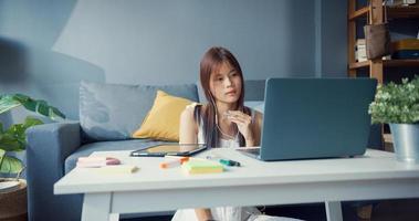 junge asiatische Mädchen Teenager mit lässigem Hemd tragen Kopfhörer mit Laptop lernen online Vorlesung im Laptop im Wohnzimmer im Haus schreiben. Isolieren Sie das Online-E-Learning-Konzept für die Coronavirus-Pandemie. foto