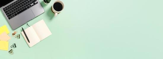 kreative flache Lage des Arbeitsplatzschreibtischs. Schreibtisch von oben mit Laptop, Kaffeetasse und offenem schwarzen Notizbuch auf grünem Hintergrund. Panoramabanner mit Kopienraum für Text- und Werbefläche. foto