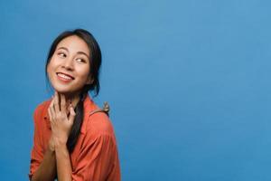 Porträt der jungen asiatischen Dame mit positivem Ausdruck, breit lächeln, in Freizeitkleidung auf blauem Hintergrund gekleidet. glückliche entzückende frohe frau freut sich über erfolg. Gesichtsausdruck Konzept. foto